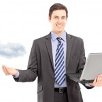 Young male in a suit holding a laptop, symbolizing cloud computing