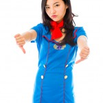 Unhappy Asian air stewardess giving thumbs down gesture