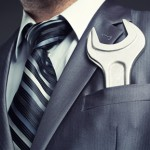 Man in suit with wrench in pocket